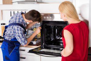 repairman fixing oven appliance